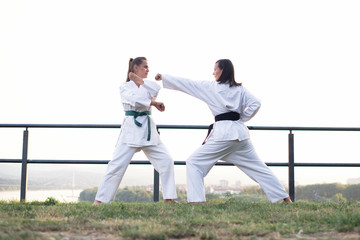 Two fit young women dressed in white kimono training karate martial arts in nature.