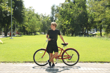 Attractive man with bike outdoors on sunny day