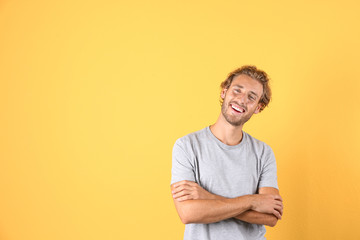 Handsome young man laughing on color background. Space for text Wall mural