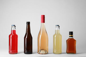 Bottles with different alcoholic drinks on light background