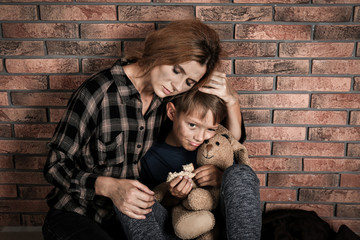 Poor woman hugging her son near brick wall