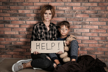 Poor woman with her son asking for help near brick wall