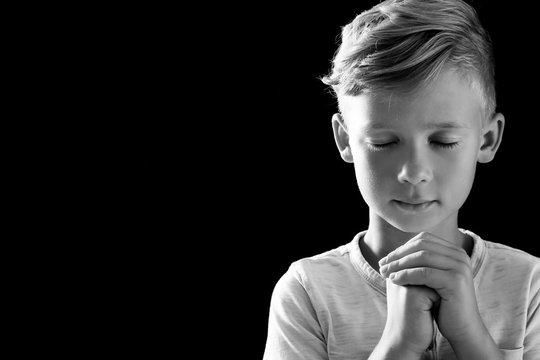Little boy with hands clasped together for prayer on dark background, black and white effect. Space for text