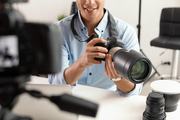 Male photo blogger recording video on camera indoors