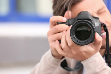 Male photographer with professional camera on blurred background. Space for text