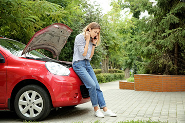 Woman talking on phone near broken car outdoors