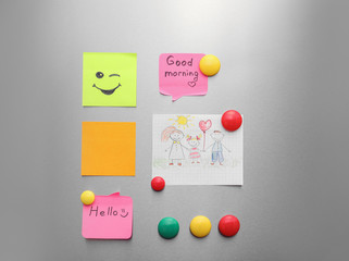 Paper sheets, child's drawing and magnets on refrigerator door