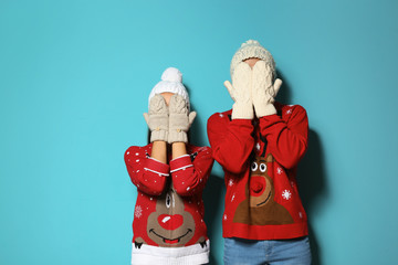 Young couple in Christmas sweaters and knitted hats on color background