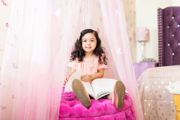 Girl Going Through Book On Seat In Princess Bedroom
