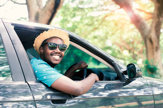 African man driver Wearing sunglasses and smiling while sitting in a car with open front window.