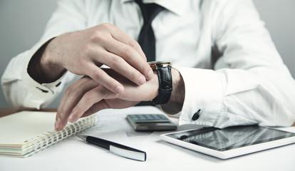 Businessman adjusting his wristwatch. Business concept