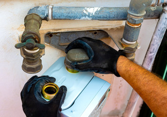 Worker removes the seals to the fitting between the pipe and gas meter. Selective focus
