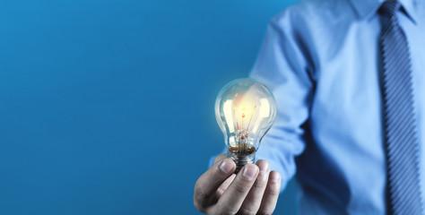 Businessman holding light bulb. Concept of new idea