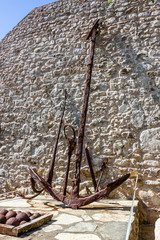 Old rusty sea ship anchors standing at the ancient stone wall.