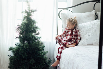 Girl sitting on a bed looking at a Christmas tree