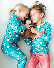 Two girls playing with a teddy bear,