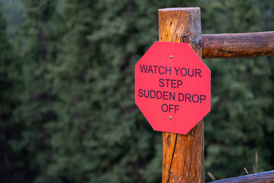 Sign post warns hikers and pedestrians to Watch Your Step Sudden Drop Off for a nearby cliff