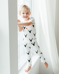 Smiling boy standing on a window sill