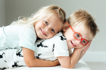 Blond sister hugging her brother on bed