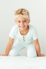 Smiling boy kneeling on a bench
