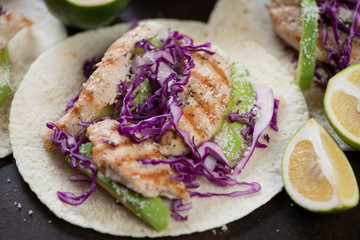 Close-up of tacos with red cabbage, grilled chicken fillet, avocado, lime and cheese, selective focus