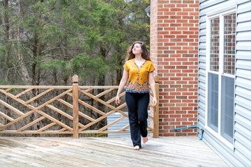 One young woman walking outside, outdoors barefoot on wooden house, home deck, looking up, homeowner at backyard, front yard