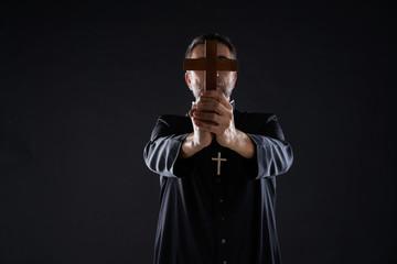 Priest holding cross of wood praying