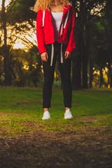 Crop sportive woman standing on meadow