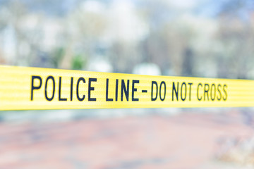Police Line do not cross caution tape in Washington DC, USA Secret Service security by White House in capital city closeup isolated yellow color