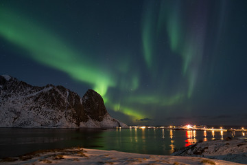 Northern light display over Reinefjorden (Lofoten) in winter