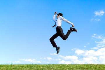 青空をバックにジャンプするYシャツ姿の若いビジネスマン1人。元気・パワー・喜び・挑戦イメージ