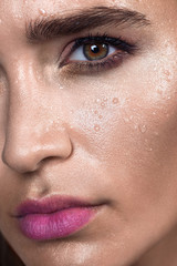 Close up gamour beauty woman portrait. Fashion wet shiny skin, with drops sexy gloss lips make-up and pink eyebrows