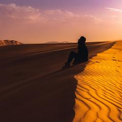 silhouette of girl on the sand dune in Sahara Desert at sunset