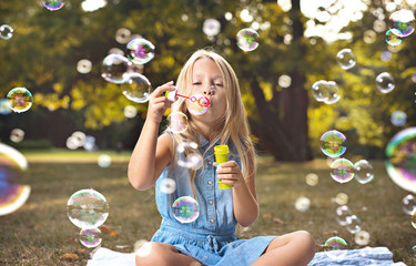 Photo sur Plexiglas Artiste KB Portrait of a cheerful girl blowing soap bubbles