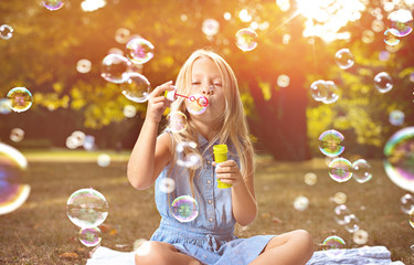 Poster Artist KB Portrait of a cheerful girl blowing soap bubbles