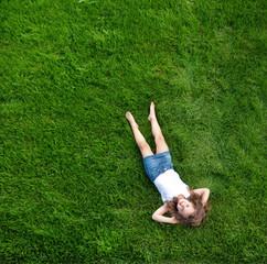 Foto auf AluDibond Artist KB Relaxed little girl lying on a fresh, green lawn