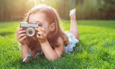 Cute little girl lying on green lawn and taking a picture