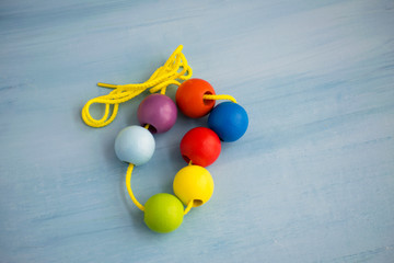 Developmental children's toy. Colored wooden balls on a rope. Colorful wooden baby beads for necklace.