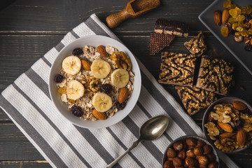 Oatmeal with bananas in white bowl on striped napkin on gray natural desk.