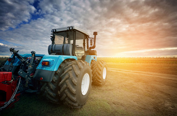 Wall Mural - Tractor working in the field in the background of the sunset