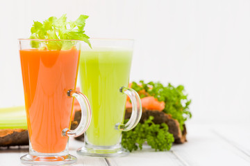 Carrot and celery juice with fresh vegetables on bark plates on wooden background.