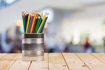 Colorful pencils in jar and red apple on table