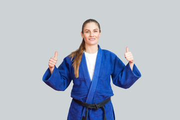 Foto auf Acrylglas Kampfsport Positive athletic karate woman in blue kimono with black belt standing, showing thumbs up and looking at camera with toothy smile. Japanese martial arts concept. Indoor, studio shot, gray background