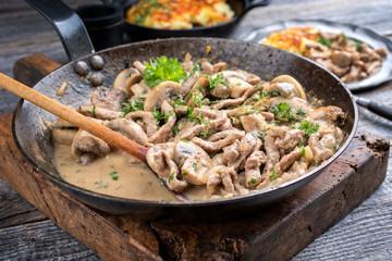 Traditional Swiss zürcher geschnetzeltes with rösti as closeup in a wrought-iron pan