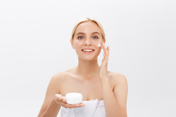 Close up beauty portrait of a laughing beautiful half naked woman applying face cream and looking away isolated over white background.