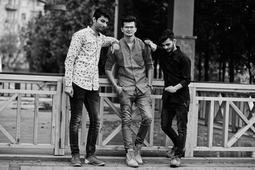 Three indian guys students friends walking on street. Black and white photo.
