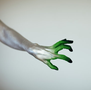 Creepy Halloween monster witch hand with white, green and black in front of white background