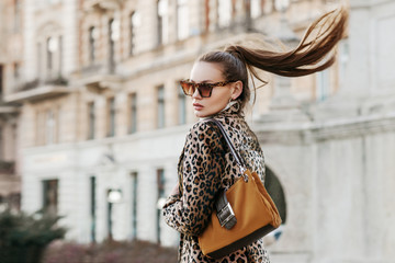 Outdoor close up fashion portrait of young beautiful fashionable woman wearing  sunglasses, leopard print blazer, holding brown suede bag, walking in street of european city. Copy, empty space