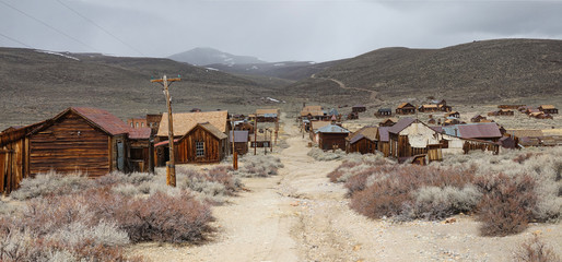Empty gravel road runs through a ghost town in the harsh American wilderness. Wall mural