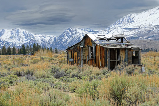 Lonely wooden cabin decaying in the rugged wilderness under the snowy mountains.